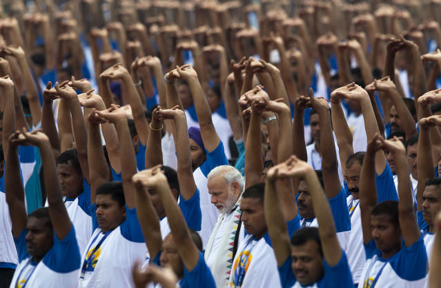FILE - In this June 21, 2016 file photo, India's Prime Minister Narendra Modi, center,practices yoga along with thousands of Indians to mark the second International Yoga Day, in Chandigarh, India. Indian Prime Minister Narendra Modi's party claimed it had won re-election with a commanding lead in vote count Thursday, May 23, 2019. Modi, 68, the leader of the Hindu nationalist Bharatiya Janata Party, has carefully constructed an image of himself as a pious man of the people, a would-be monk called to politics who has elevated India's status globally and transformed its parliamentary elections from a contest of political parties on social and economic issues into a cult of personality. (AP Photo/Saurabh Das, File)