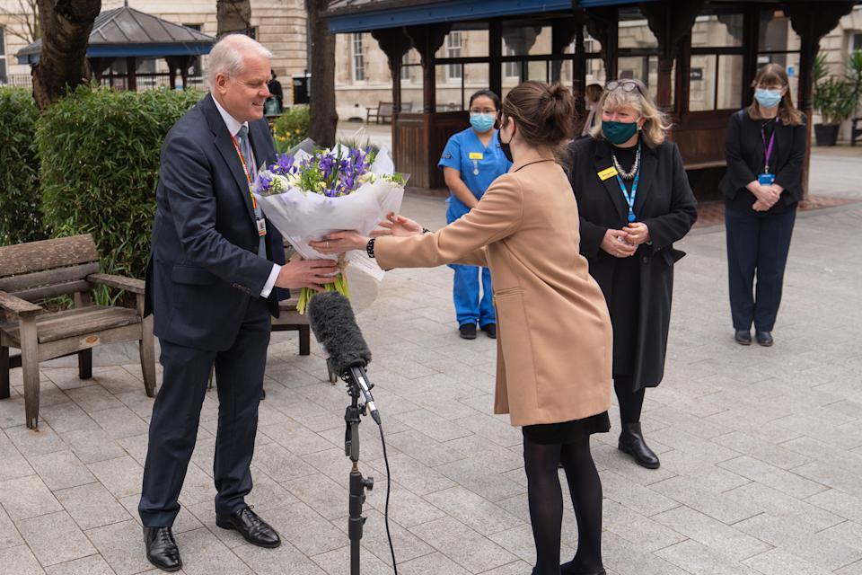 Chief Executive of St Bartholomew's Hospital Professor Charles Knight receives flowers from Queen Elizabeth II during a ceremony at St Bartholomew's Hospital, London on the anniversary of the first national lockdown to prevent the spread of coronavirus. Picture date: Tuesday March 23, 2021. (Photo by Dominic Lipinski/PA Images via Getty Images)