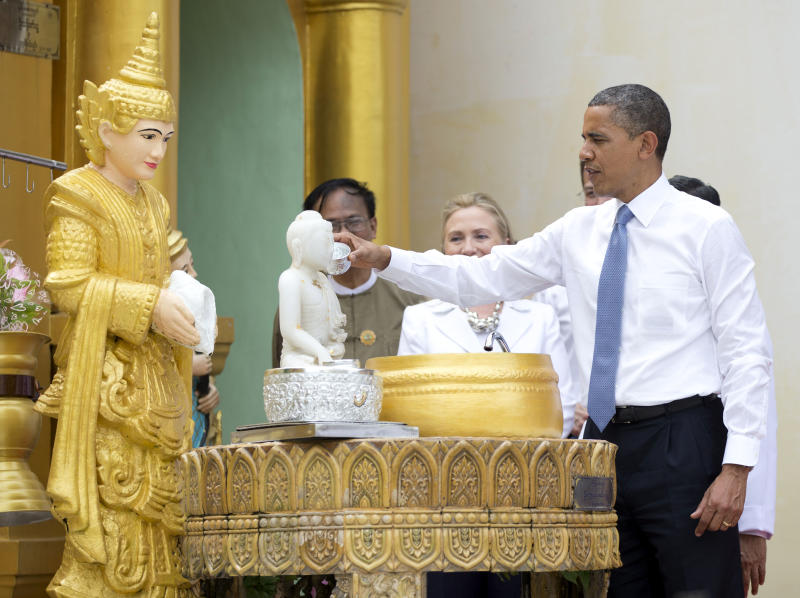 "FILE - In this Nov. 19, 2012, photo, President Barack Obama ""douses eleven flames"" as he tours the Shwedagon Pagoda with Secretary of State Hillary Rodham Clinton in Yangon, Myanmar. Little noticed during Obama's landmark visit to Myanmar was a significant concession that could shed light on whether that nation's powerful military pursued a clandestine nuclear weapons program, possibly with North Korea's help. Myanmar announced it would sign an international agreement that would require it to declare all nuclear facilities and materials. Although it would be up to Myanmar to decide what to declare, it could provide some answers concerning its acquisition of dual-use machinery and military cooperation with North Korea. (AP Photo/Carolyn Kaster)"