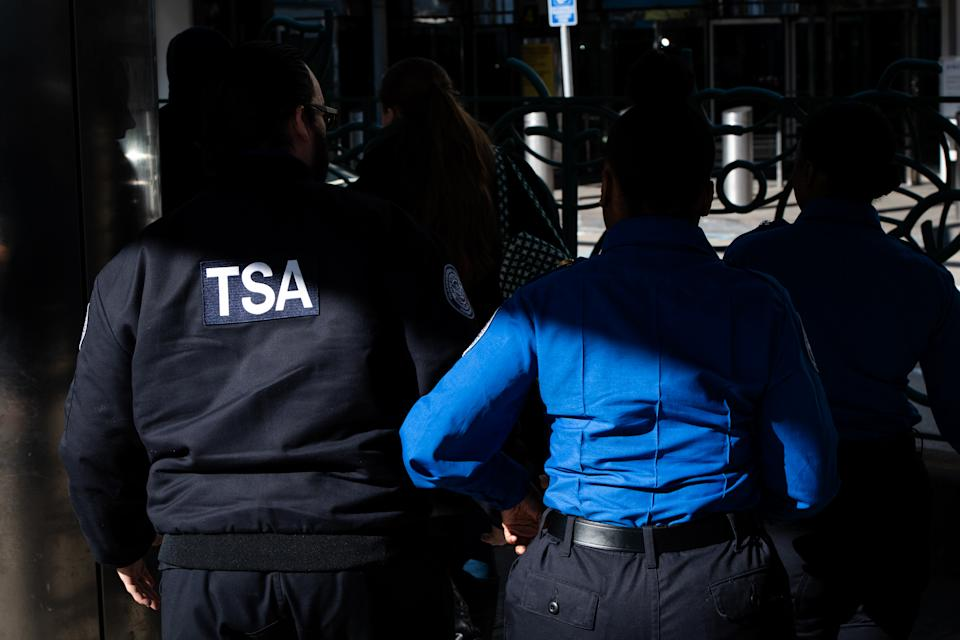 TSA agents walk through LaGuardia Airport in Queens, N.Y.