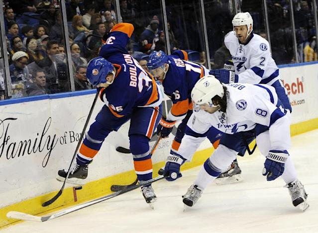 New York Islanders' Eric Boulton (36) and Tampa Bay Lightning' Mark Barberio (8) battle for the puck around the boards as Islanders' Peter Regin (16) and Lightning Eric Brewer (2) follow behind in the second period of an NHL hockey game on Tuesday, Dec. 17, 2013, in Uniondale, N.Y. (AP Photo/Kathy Kmonicek)