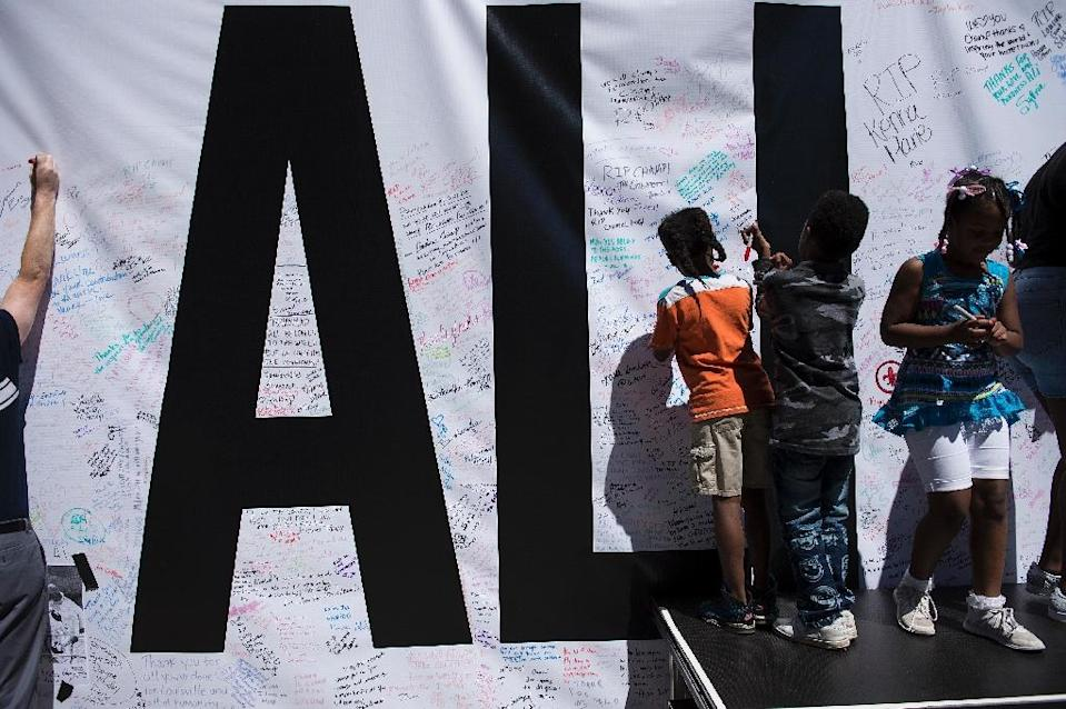 People leave messages in memory of Muhammad Ali on an banner outside the Performing Arts Center in Louisville, Kentucky (AFP Photo/Brendan Smialowski)
