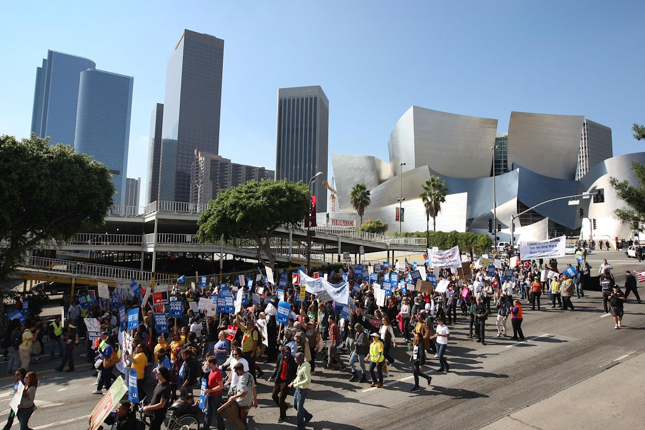 LOS ANGELES, CA - NOVEMBER 5:  Occupy LA protesters pass Disney Hall (R) during the Move Your Money March on what is being called Bank Transfer Day on November 5, 2011 in Los Angeles, California. Occupy movement members are calling for people to move their money from banks to credit unions today in support of the 99% movement.   (Photo by David McNew/Getty Images)