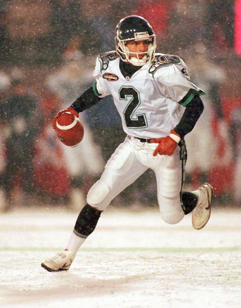 FILE - This Nov. 24, 1996, file photo shows Toronto Argonauts' quarterback Doug Flutie scrambling against the Edmonton Eskimos during first half action at the Grey Cup in Toronto. For those wondering what the effects might be if the NFL goes through with its bid to expand from 16 to 18 regular-season games, take it from those who've been through it: It's a grind.  (AP Photo/Frank Gunn, File)