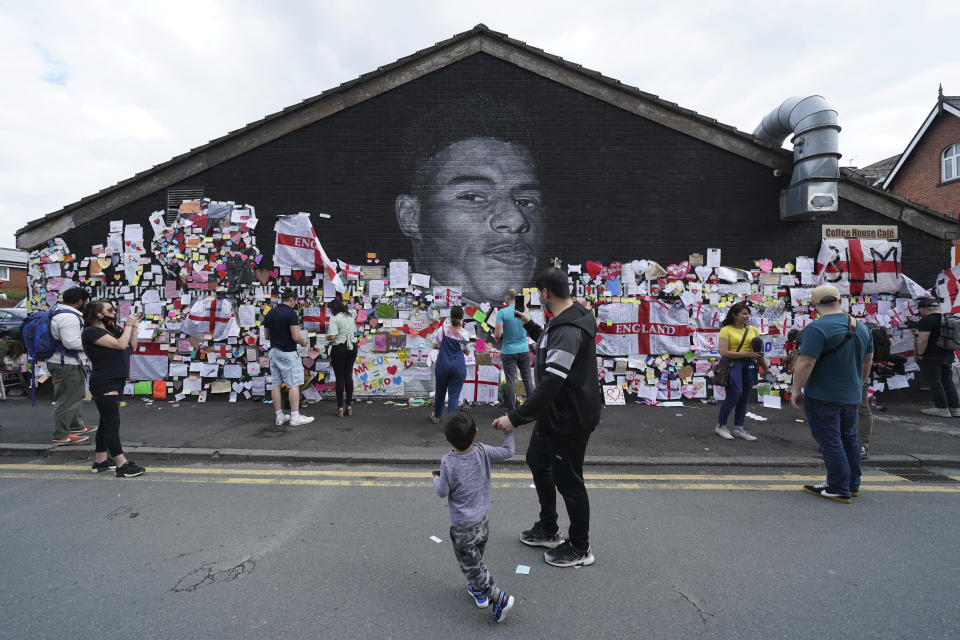 People look at the messages of support left on a mural of Manchester United striker and England player Marcus Rashford, on the wall of the Coffee House Cafe on Copson Street, in Withington, Manchester, England, Tuesday July 13, 2021. The mural was defaced with graffiti in the wake of England losing the Euro 2020 soccer championship final match to Italy. (AP Photo/Jon Super)