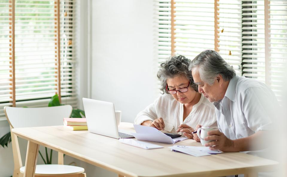 Stressed Asian Senior Couple using calculator and calculate family budget, Debts, monthly expenses in home during Financial economic crisis. Senior man and woman looking at account book, bill, passbook, receipt and laptop computer on table.