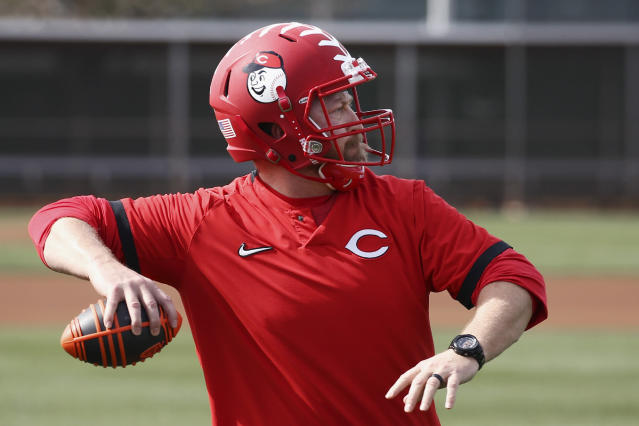 Cincinnati Reds strength coach Sean Marohn wears a football helmet as he throws a football to an outfielder as they warm up during baseball spring training Friday, Feb. 21, 2020, in Goodyear, Ariz. (AP Photo/Ross D. Franklin)