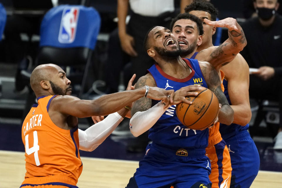 Denver Nuggets guard Monte Morris (11) drives between Phoenix Suns' Jevon Carter (4) and Abdel Nader during the first half of an NBA basketball game Friday, Jan. 22, 2021, in Phoenix. (AP Photo/Rick Scuteri)