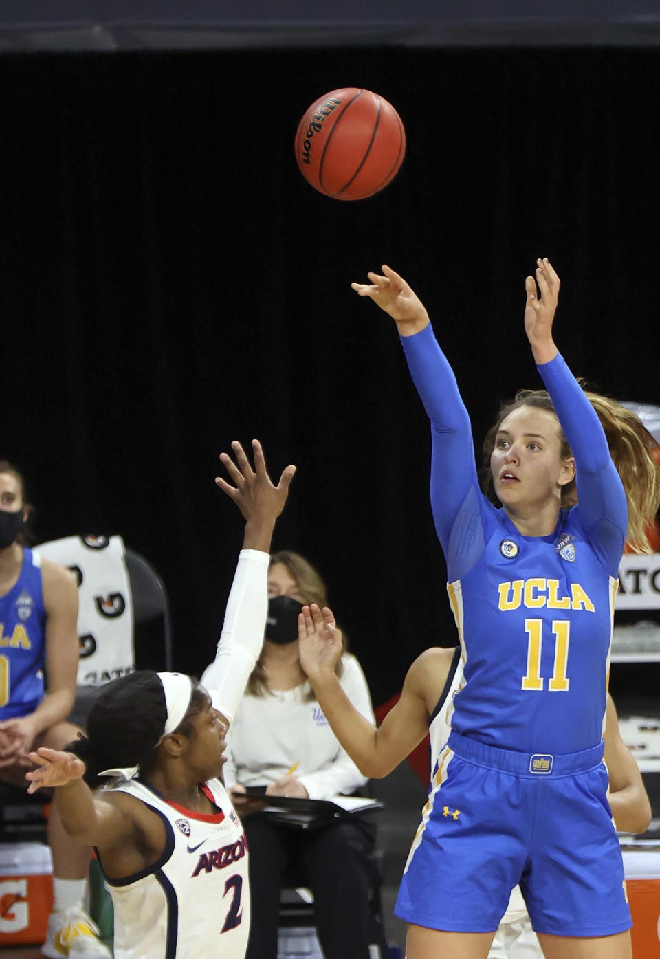 UCLA forward Emily Bessoir (11) shoots as Arizona guard Aari McDonald (2) defends during the second half of an NCAA college basketball game in the semifinals of the Pac-12 women's tournament Friday, March 5, 2021, in Las Vegas. (AP Photo/Isaac Brekken)