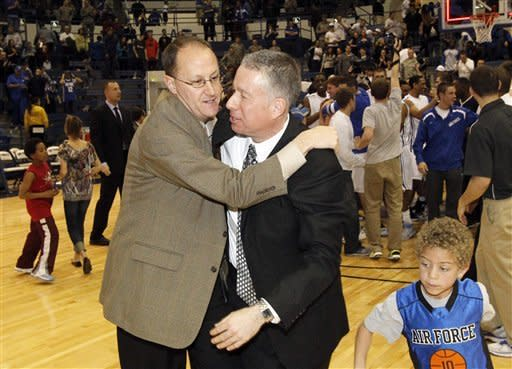 Troy Garnhart, left, associate athletic director of communications at Air Force Academy, hugs head coach Dave Pilipovich after Air Force's 58-56 victory over San Diego State in an NCAA college basketball game at Air Force Academy, Colo., on Saturday, Feb. 18, 2012. (AP Photo/David Zalubowski)