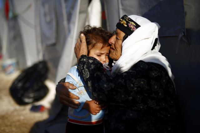 A Kurdish refugee woman from the Syrian town of Kobani hugs a child outside her tent in a camp in the southeastern town of Suruc, Sanliurfa province October 22, 2014. REUTERS/Kai Pfaffenbach (TURKEY - Tags: MILITARY CONFLICT POLITICS)