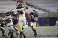 Washington quarterback Dylan Morris, right, passes under pressure from Oregon State defensive lineman Simon Sandberg (96) during the first half of an NCAA college football game Saturday, Nov. 14, 2020, in Seattle. (AP Photo/Ted S. Warren)