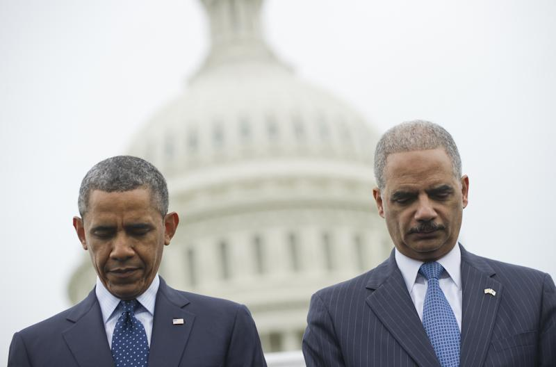 US President Barack Obama and Attorney General Eric Holder (R) bow their head in prayer as they attend the National Peace Officers Memorial Service, at the US Capitol in Washington, DC on May 15, 201 (AFP Photo/Saul Loeb)
