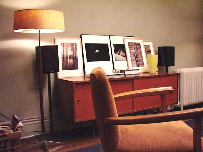 In Carrie's beloved apartment, a midcentury-style credenza displays plenty of art.