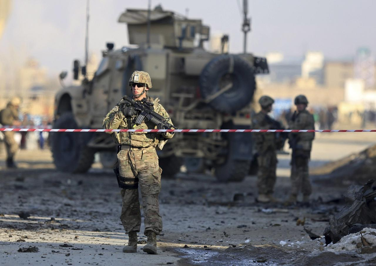U.S. troops stand guard at the site of a suicide car bomb attack in Kabul, February 10, 2014. A suicide bomber in a car targeted a convoy of vehicles carrying foreign forces in the eastern part of Afghan capital, Kabul on Monday. REUTERS/Omar Sobhani (AFGHANISTAN - Tags: CIVIL UNREST MILITARY)