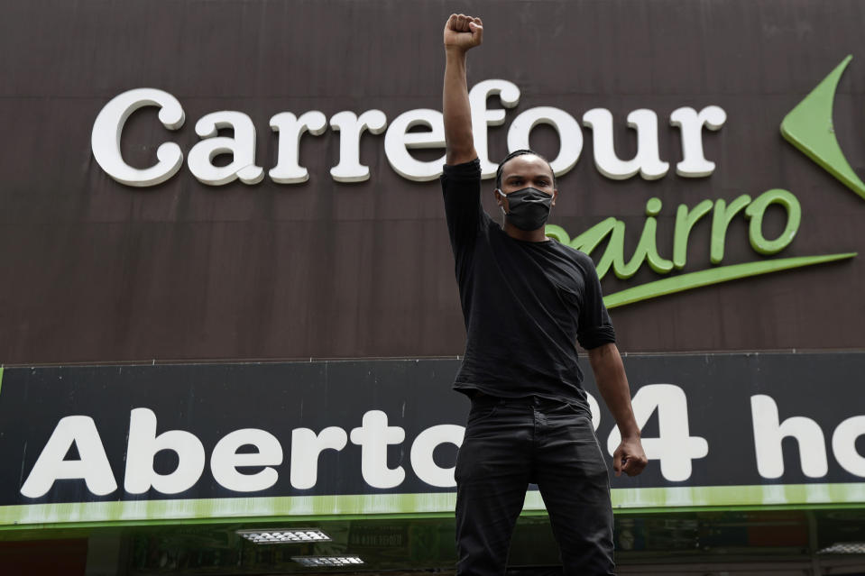 """A man shouts """"Black lives matter"""" during a protest against the murder of Black man João Alberto Silveira Freitas, which occurred at a different Carrefour supermarket the night before, outside a Carrefour supermarket in Brasilia, Brazil, Friday, Nov. 20, 2020, which is National Black Consciousness Day in Brazil. Freitas died after being beaten by supermarket security guards in the southern Brazilian city of Porto Alegre, sparking outrage as videos of the incident circulated on social media. (AP Photo/Eraldo Peres)"""