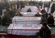 People from the Shiite Hazara community gather around caskets of coal mine workers who were killed by unknown gunmen near the Machh coal field, during a sit-in protest, in Quetta, Pakistan, Monday, Jan. 4, 2021. Gunmen opened fire on a group of minority Shiite Hazara coal miners after abducting them, killing 11 in southwestern Baluchistan province early Sunday, a Pakistani official said. (AP Photo/Arshad Butt)