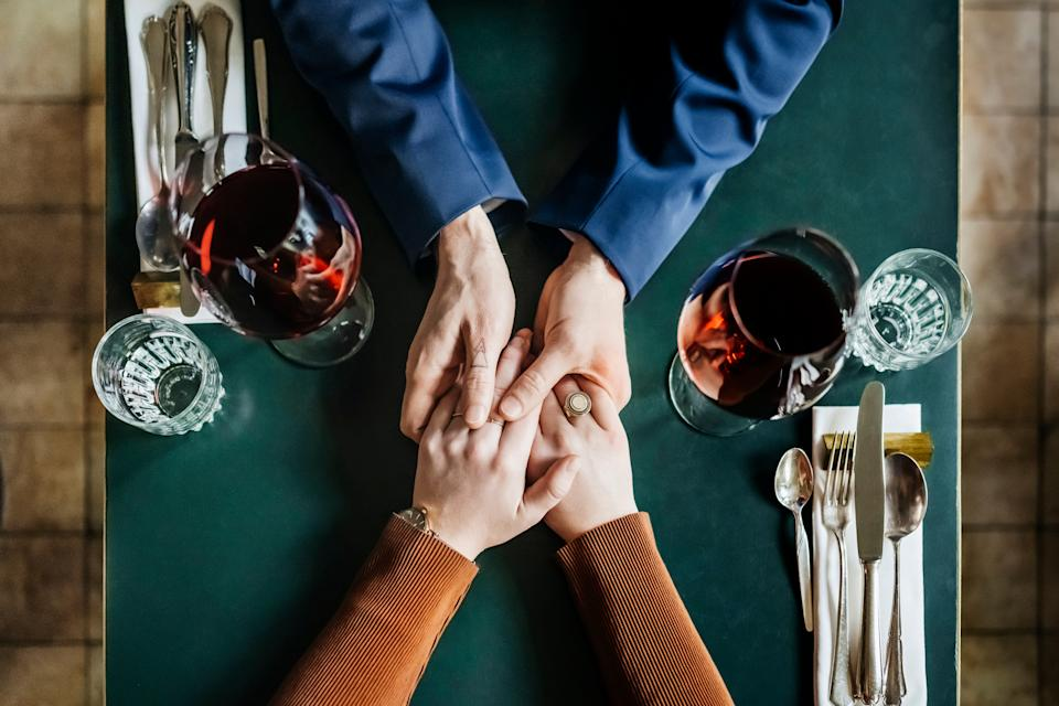 An aerial view of a couple holding hands and drinking red wine while sitting at a restaurant table for lunch together.