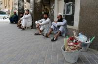 Foreign workers sit on the street after losing their jobs, following the outbreak of the coronavirus disease (COVID-19), in Riyadh