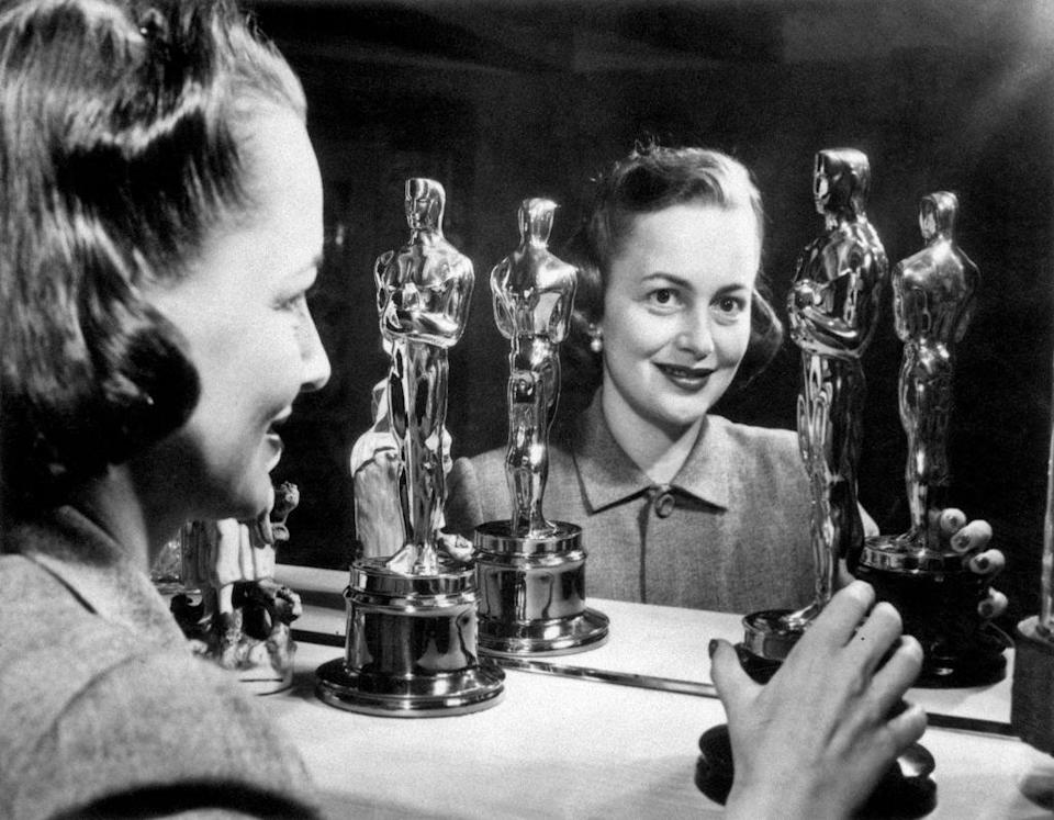 <p>The British-born actress looks in a mirror with her first two Oscars, won for the films <em>To Each His Own</em> and <em>The Heiress</em>. </p>