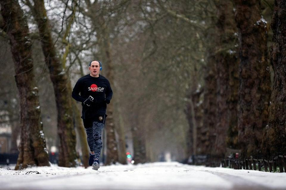 A man jogs in snow-covered St James's Park (REUTERS)
