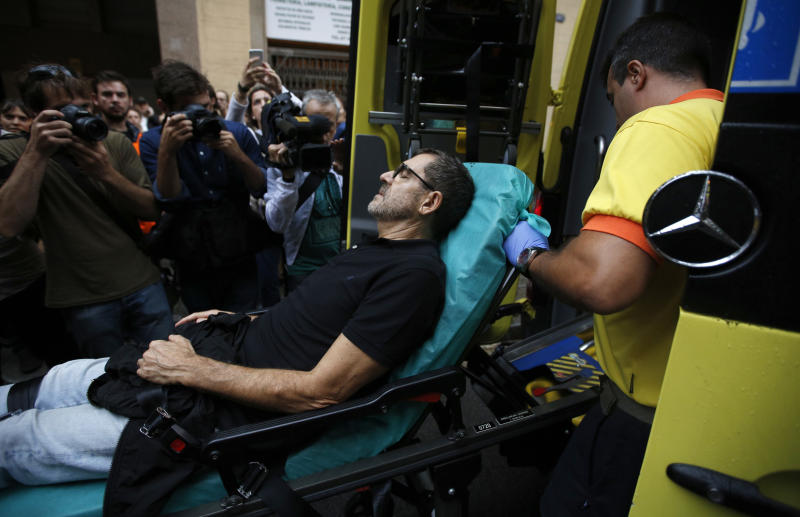 An injured man is taken into an ambulance near a school assigned to be a polling station. (AP Photo/Emilio Morenatti)