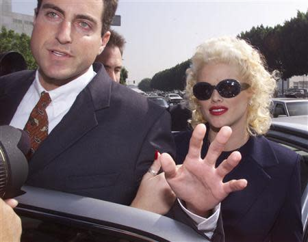 Model and former Playboy magazine Playmate Anna Nicole Smith is escorted by an unidentified attorney from her car as she arrives for opening arguments in her bankruptcy case at the Roybal Federal Building in Los Angeles, California in this October 27, 1999 file photo. REUTERS/Fred Prouser/Files