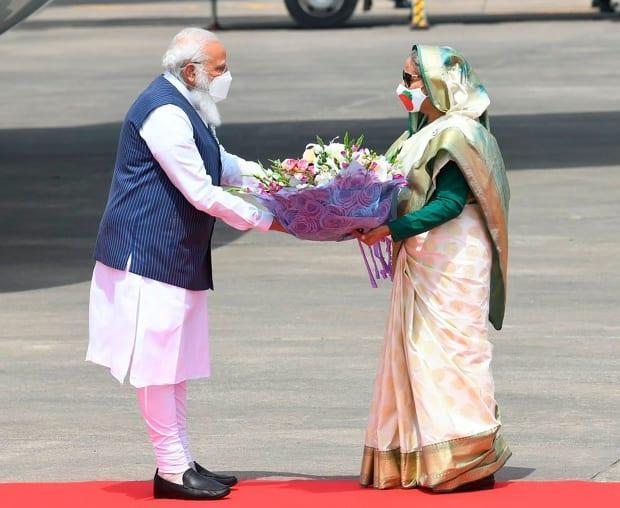 Bangladeshi Prime Minister Sheikh Hasina, right, hands a bouquet of flowers to Indian Prime Minister Narendra Modi, left, in Dhaka, Bangladesh on Friday. Bangladeshis are marking 50 years of the country's independence from Pakistan and a century since the birth of independence leader Sheikh Mujibur Rahman, the father of the current prime minister. (Prime Minister of India Narendra Modi's Twitter handle/Associated Press - image credit)