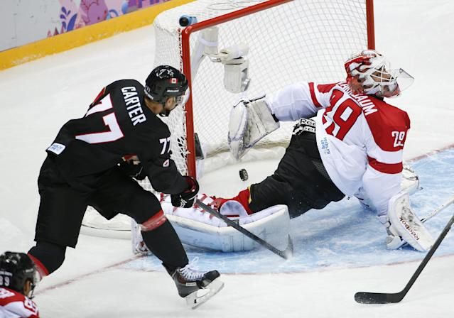 Canada forward Jeff Carter shoots and scores against Austria goaltender Bernhard Starkbaum in the second period of a men's ice hockey game at the 2014 Winter Olympics, Friday, Feb. 14, 2014, in Sochi, Russia. (AP Photo/Julio Cortez)