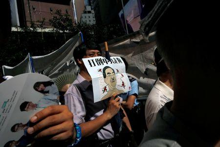 """A protester carries a defaced picture of Hong Kong's Chief Executive Leung Chun-ying, during a protest march on the day marking the 19th anniversary of Hong Kong's handover to Chinese sovereignty from British rule, in Hong Kong, China July 1, 2016. The words on poster read """"Down the Chinese communists's dog"""". REUTERS/Tyrone Siu"""