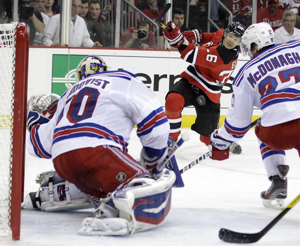 New Jersey Devils' Patrik Elias, center, of Czech Republic, takes a shot against New York Rangers goalie Henrik Lundqvist, left, of Sweden, and Ryan McDonagh during the second period of Game 3 of an NHL hockey Stanley Cup Eastern Conference final playoff series, Saturday, May 19, 2012, in Newark, N.J. (AP Photo/Julio Cortez)