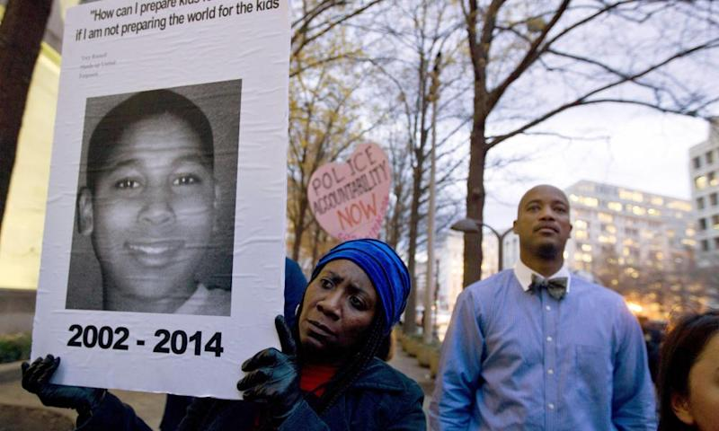Tomiko Shine holds up a poster of Tamir Rice during a protest in Washington in 2014.