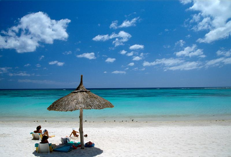 An isolated beach in Mauritius with a couple of people and a sun umbrella made of natural materials.