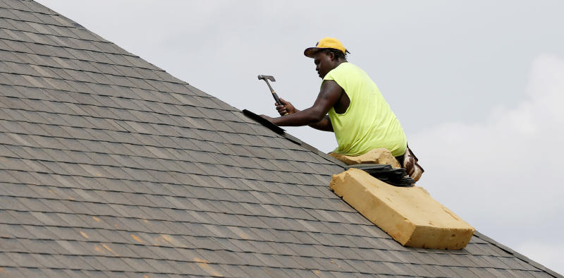 FILE - In this June 19, 2019 file, photo a worker balances on a steep roof as he lays down shingles on a roof on a new house in a Brandon, Miss., neighborhood. U.S. homebuilder stocks have been on a tear this year, with most individual companies on track to close out 2019 with gains well ahead of the broader market. (AP Photo/Rogelio V. Solis, File)