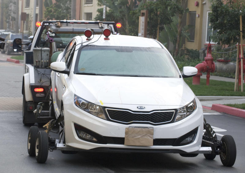 A police tow truck removes a Kia sedan from the property where two people were found shot to death inside a parked car, Sunday night, Feb. 3, 2013, in the parking structure of a condo complex in Irvine, Calif. Police in Orange County say they have no motive for a shooting that killed California State University, Fullerton assistant college basketball coach Monica Quan and her fiance, Keith Lawrence, whose bodies were found in a parked car. (AP Photo/The Orange County Register, Sam Gangwer) MAGS OUT; LOS ANGELES TIMES OUT