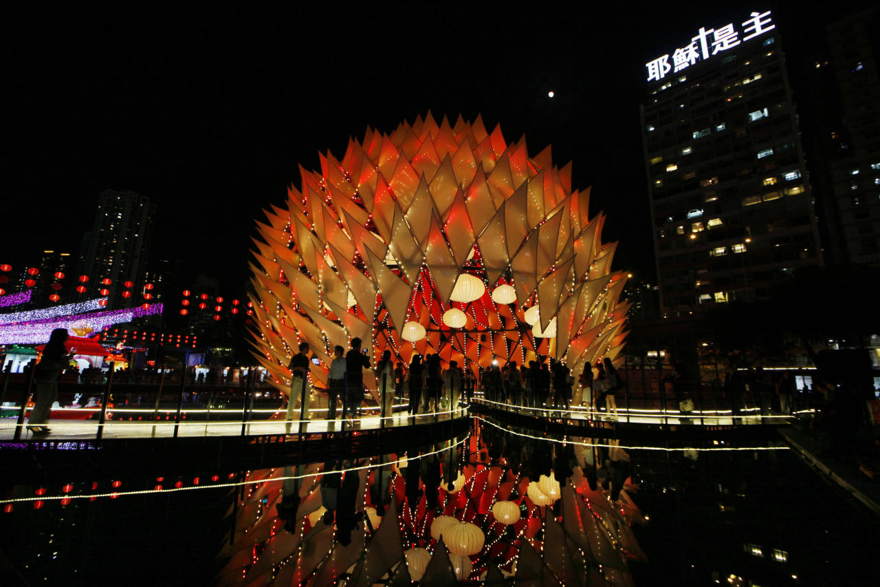 Visitors tour the illuminated decorations and lighting of small bulbs set up at popular Victoria Park to celebrate the Chinese Mid-Autumn Festival in Hong Kong Thursday, Sept. 27, 2012. Like ancient Chinese poets, Hong Kong people appreciate the beauty of the full moon in the Mid-Autumn Festival, which falls on Sunday Sept. 30 this year.  (AP Photo/Kin Cheung)