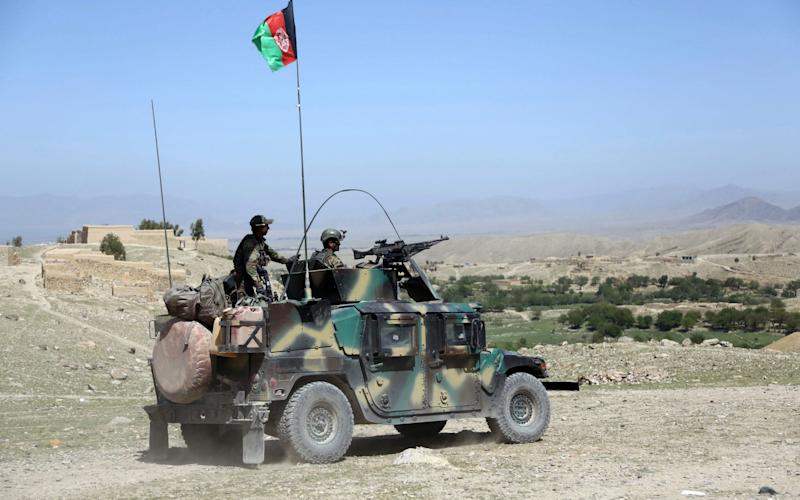 Afghan commandos patrol Pandola village near the site of a U.S. bombing in the Achin district of Jalalabad, east of Kabul - Credit: AP
