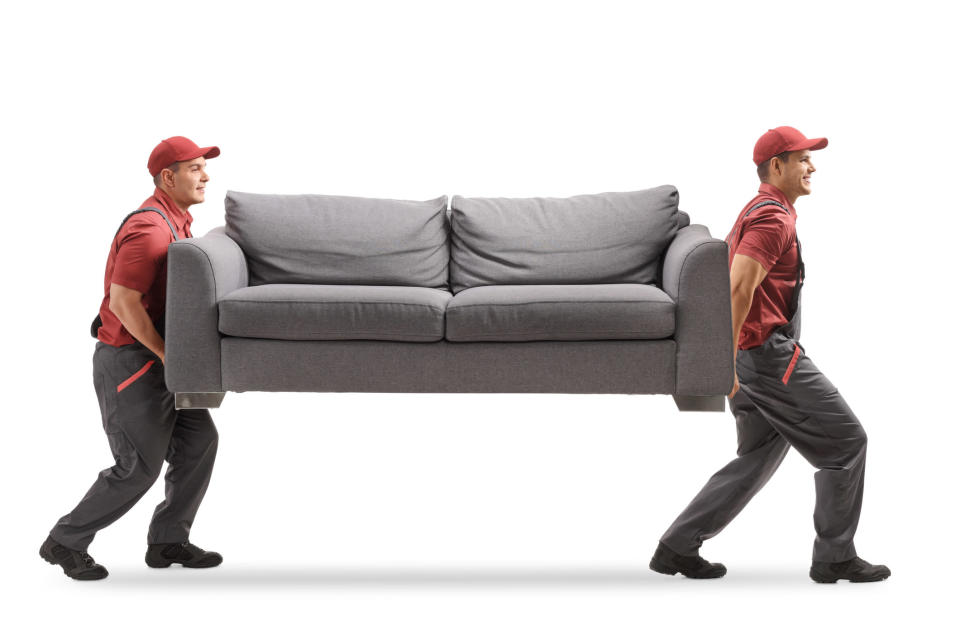 Full length profile shot of two movers carrying a couch isolated on white background