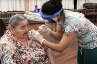 In this undated photo, provided by Paul Apfelbeck, community health aide Nicole Gregory, right, administers a COVID-19 vaccine to Virginia Johnston at the Yukon-Koyukuk Elder Assisted Living Facility in Galena, Alaska. Alaska's highest vaccination rates among those 16 or older have been in some of its remotest, hardest-to-access communities, where the toll of past flu or tuberculosis outbreaks hasn't been forgotten. (Paul Apfelbeck/Galena Interior Learning Academy via AP)