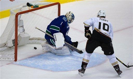 Vancouver Canucks' goalie Roberto Luongo allows a goal to Anaheim Ducks' Teemu Selanne, of Finland, (not pictured) as Anaheim's Corey Perry watches during the second period of an NHL hockey game in Vancouver, British Columbia on Saturday, Jan. 19, 2013. (AP Photo/The Canadian Press, Darryl Dyck)