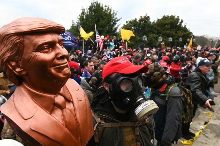 A supporter of US President Donald Trump wears a gas mask and holds a bust of him after he and hundreds of others stormed stormed the Capitol building