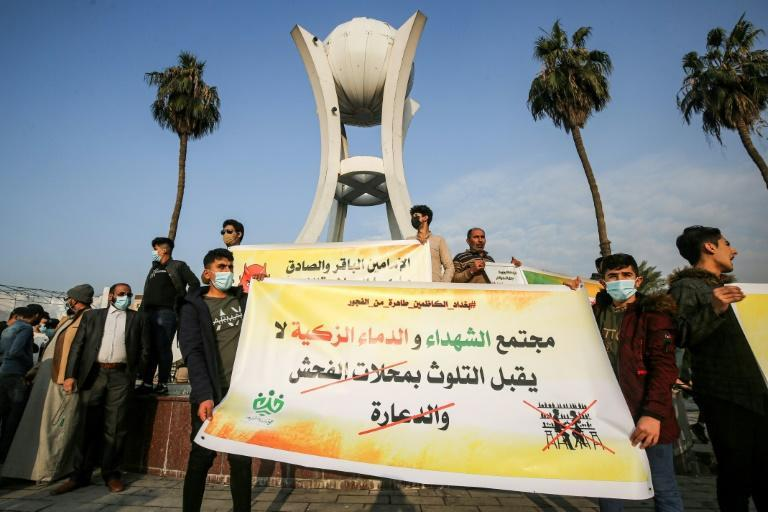 Youths from a group calling itself Tajammu' Shabab al-Sharia (Sharia Youth Rally) hold up a banner condemning liquor stores and brothels, during a demonstration in the Iraqi capital this month