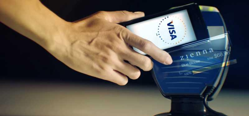 A person uses a cell phone for a mobile payment via Visa.