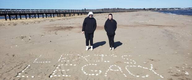 Piper and Brennah Daken with a message in shells on the beach in Bouctouche last weekend.