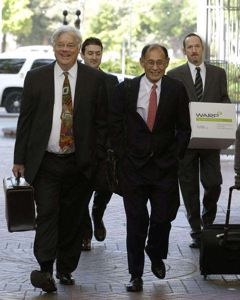 Apple attorneys Harold McElhinny, left, and William Lee, walk with others to a federal courthouse in San Jose, Calif., Monday, April 28, 2014. Dueling expert witnesses were called back to the stand Monday in a San Jose federal courtroom to discuss whether the ruling in a legal dispute between Apple and Motorola has any effect on the Apple and Samsung trial. (AP Photo/Jeff Chiu)