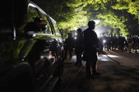 Portland police officers walk through the Laurelhurst neighborhood after dispersing protesters from the Multnomah County Sheriff's Office early in the morning on Saturday, Aug. 8, 2020 in Portland, Ore. (AP Photo/Nathan Howard)