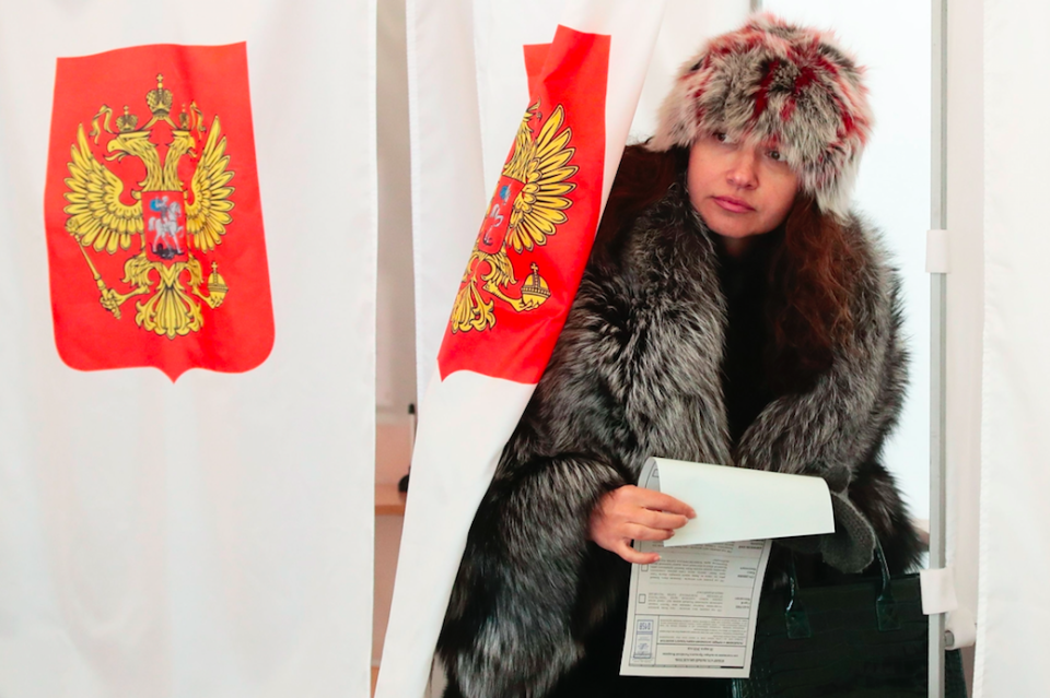 <em>A woman exits a polling booth in Moscow as she prepares to vote (PA)</em>
