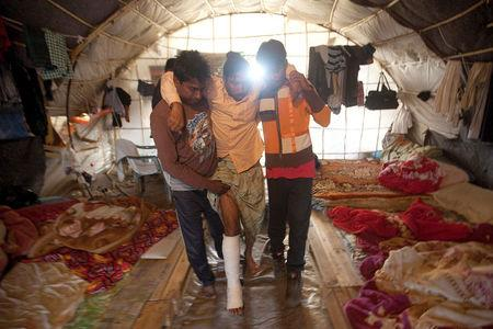 FILE PHOTO: Bangladeshi worker Mohamed (C), 25, is helped by colleagues into a tent following a shooting incident in the of town of Manolada, Greece, April 18, 2013.  REUTERS/Giorgos Moutafis/File Photo