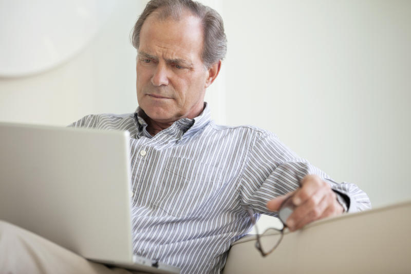 A mature man closely reading material on his laptop.