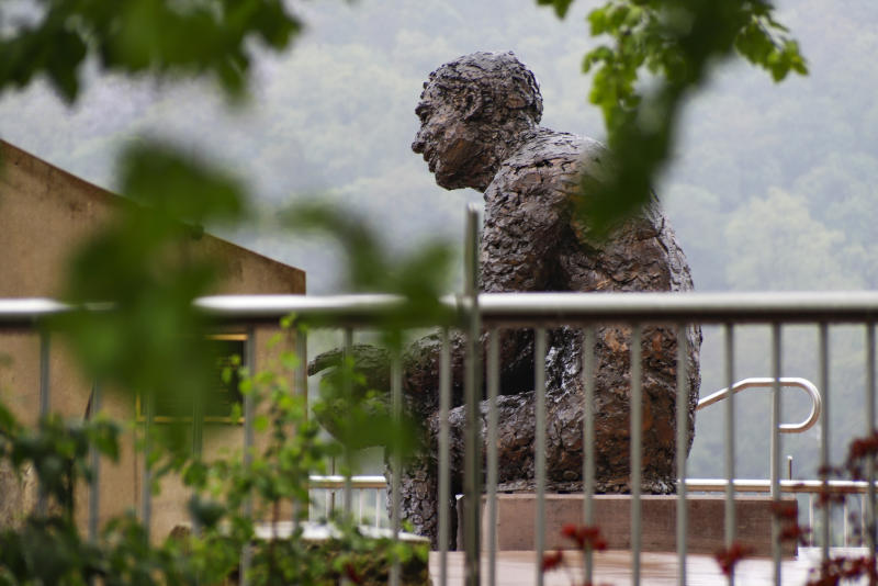 """The statue of Public Broadcasting Service's Fred Rogers, the host of children's program """"Mister Rogers' Neighborhood,"""" is visible behind the fencing in the closed-off park area where the statue is located, during this year's """"1-4-3 Day,"""" Friday, May 22, the 143rd day of 2020, in Pittsburgh. In 2019, Pennsylvania Gov. Tom Wolf declared May 23, 2019, the first """"1-4-3 Day,"""" as a day of kindness in honor of Public Broadcasting Service's Fred Rogers, the host of children's program """"Mister Rogers' Neighborhood."""" Rogers, a Pennsylvania native who died in 2003, used 143 as his special code for """"I Love You,"""" based on the number of letters in each word. (AP Photo/Keith Srakocic)"""